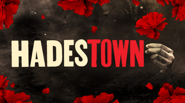 HADESTOWN Show Title with a Singular Outstretched Hand Holding a Red Carnation